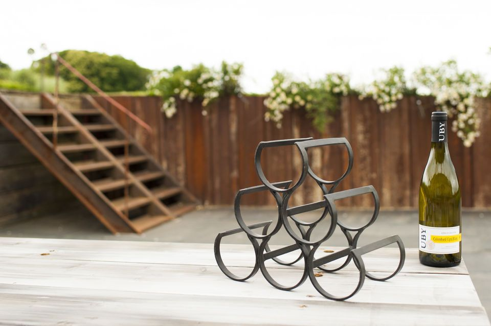 A pyramid-shaped metal rack for in a industrial decor with 6 round shape storage spaces to insert 6