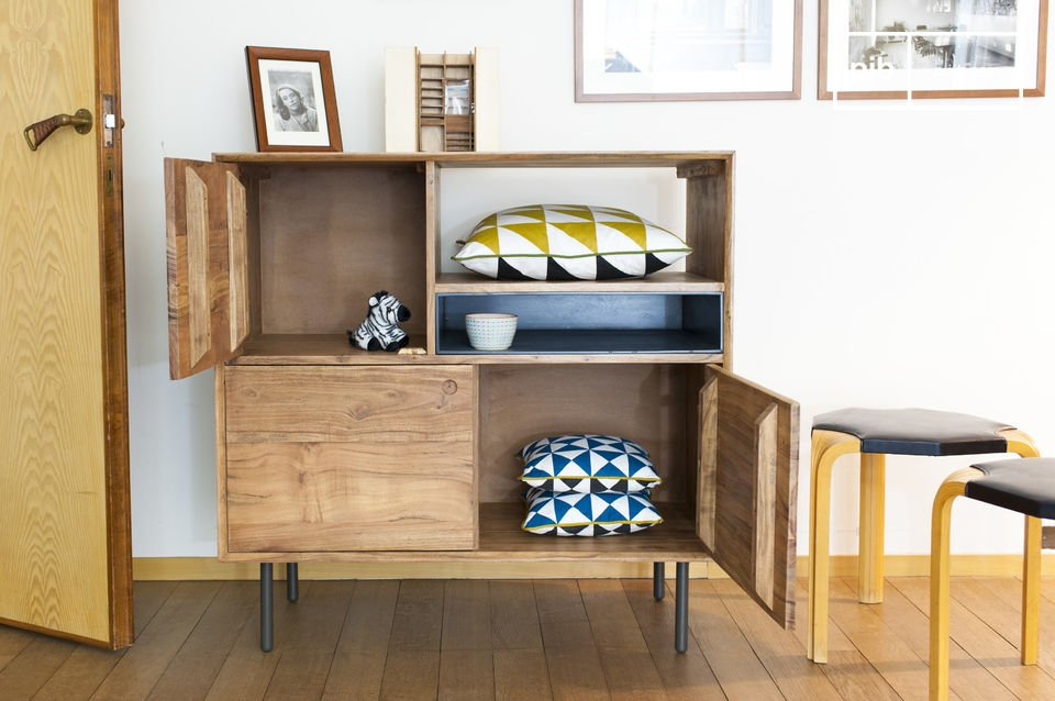 The round handles and the blue grey central storage add some retro style to this furniture