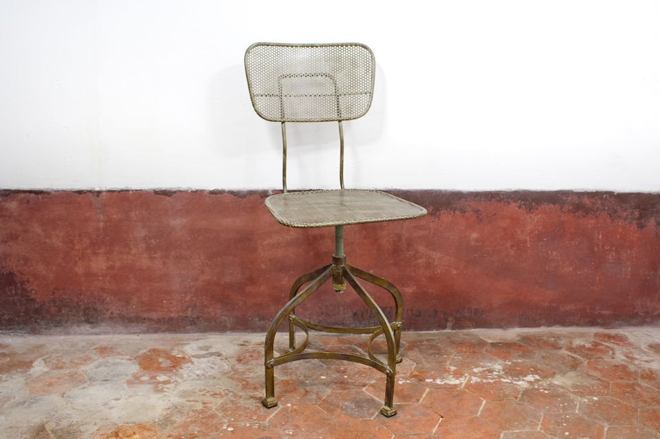 This industrial chair has vintage style as it is made of perforated metal sheeting that has been painted green and coated with distressed varnish