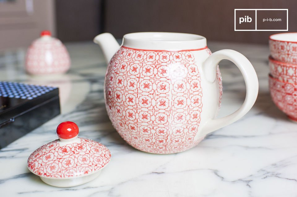 It has the classic shape of a tea pot but differs from traditional tea pots due to its red geometric patterns, painted on its white background