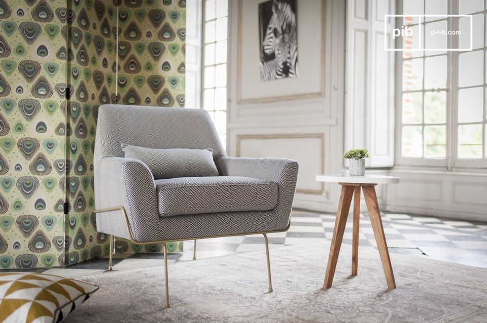 A pretty grey armchair on its very fine legs.