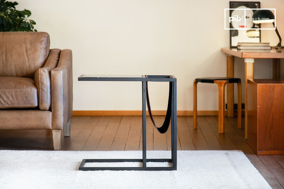 Furniture combining black veined marble top and side magazine rack.