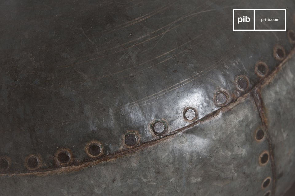 This object is been designed entirely in riveted metal, showing signs of wear which give it a vintage industrial look