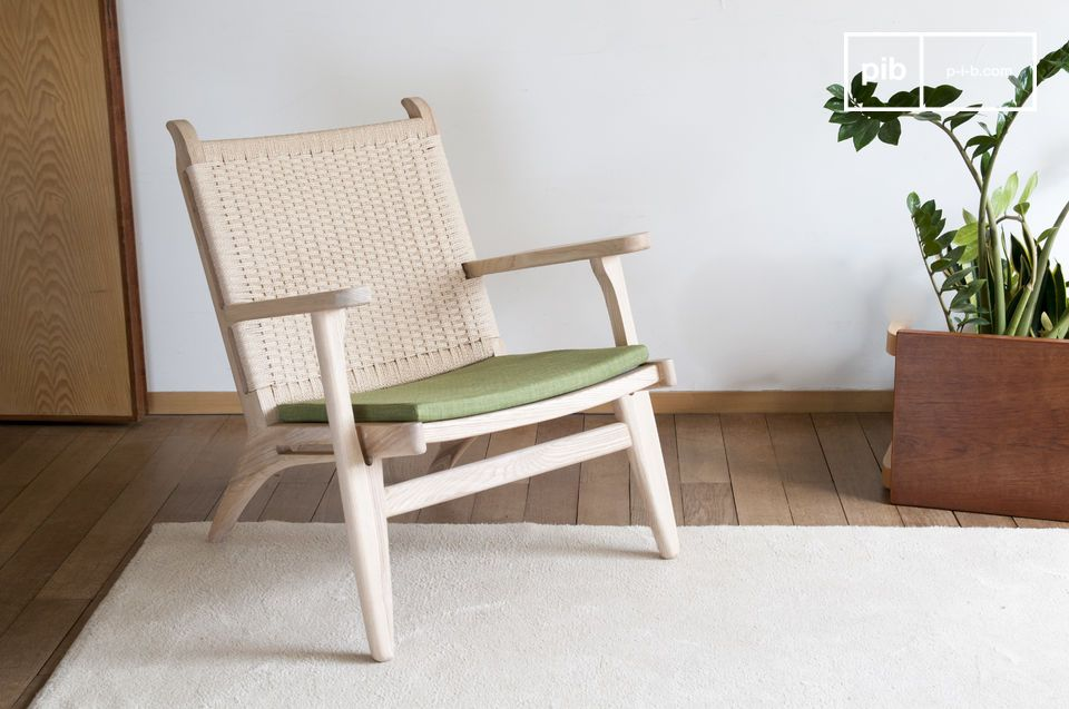 A natural armchair combining olive green, blond wood and woven rattan