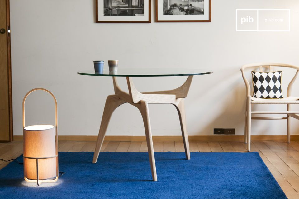 The retro lines of an arty round table combining glass and wood