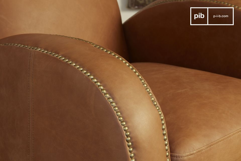 The camel tones of the armchair are enhanced by a beautiful brushed brass nailing work.