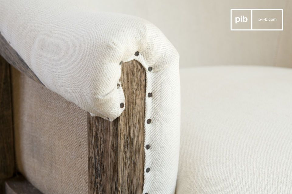 The white fabric is nicely studded on the wooden armrests.