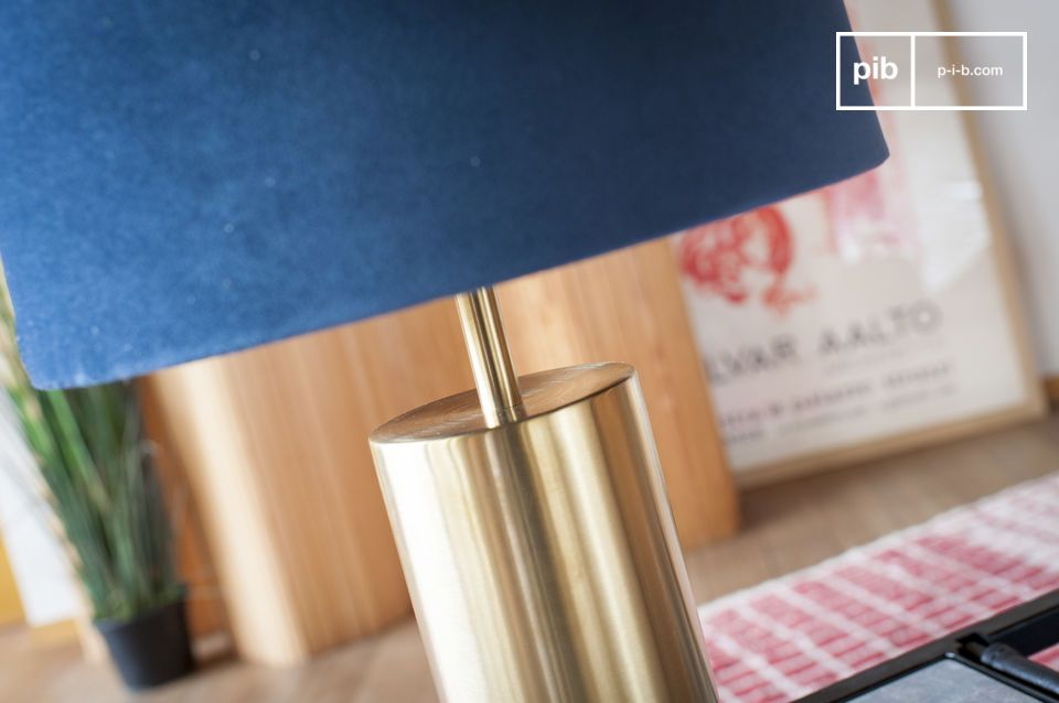 Cylindrical lamp base in brushed brass has a golden hue.