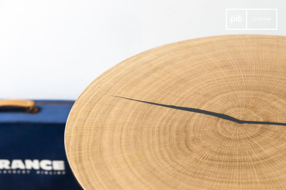 The small Xyleme side table is composed of a thin round metal top covered with oak wood